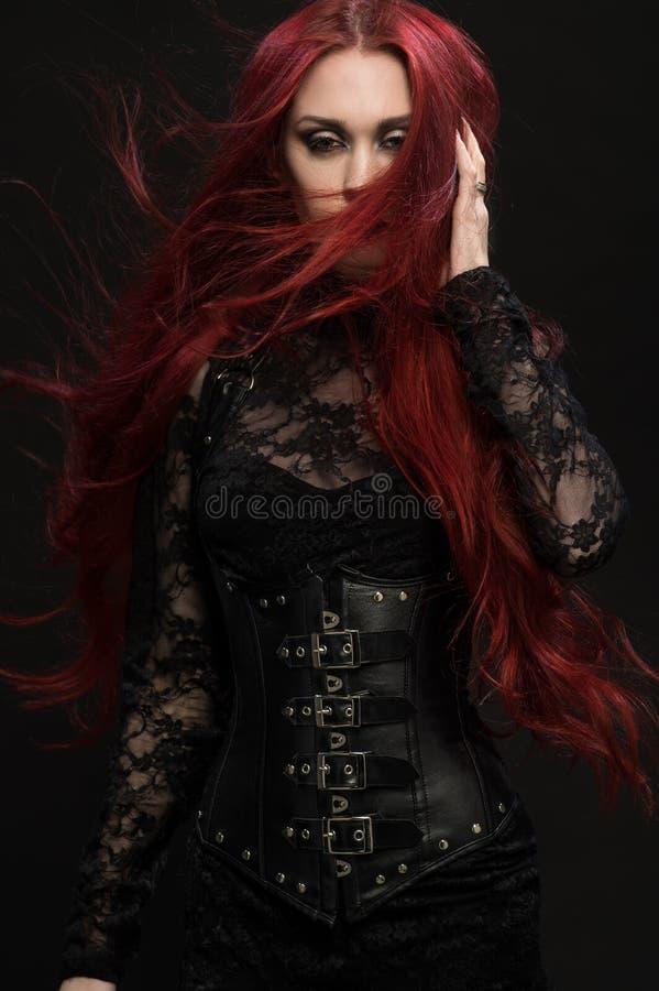 Mujer joven con el pelo rojo en traje gótico negro imágenes de archivo libres de regalías