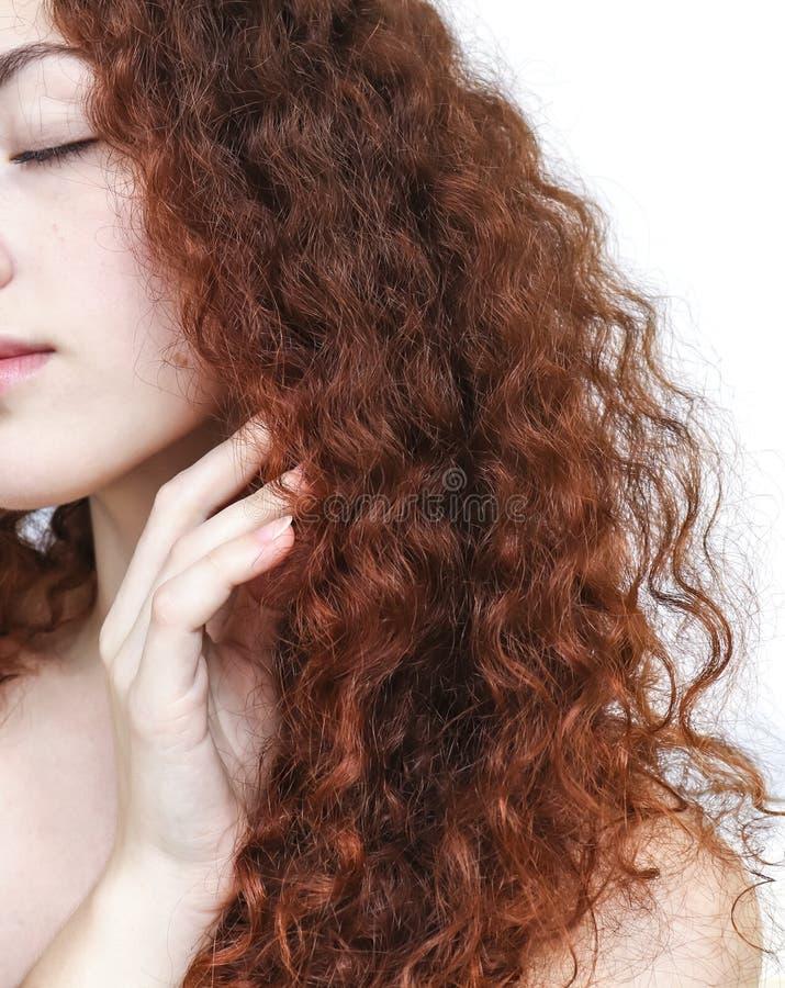 Mujer joven con el pelo rojo rizado largo imagen de archivo
