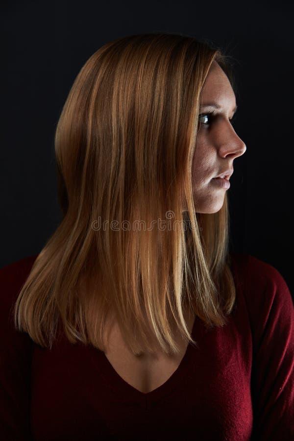 Mujer joven con el pelo rubio en perfil imagenes de archivo