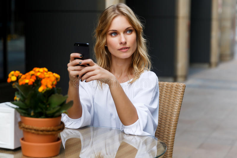 Mujer joven con el pelo rubio ondulado en el café que sostiene el teléfono fotografía de archivo libre de regalías