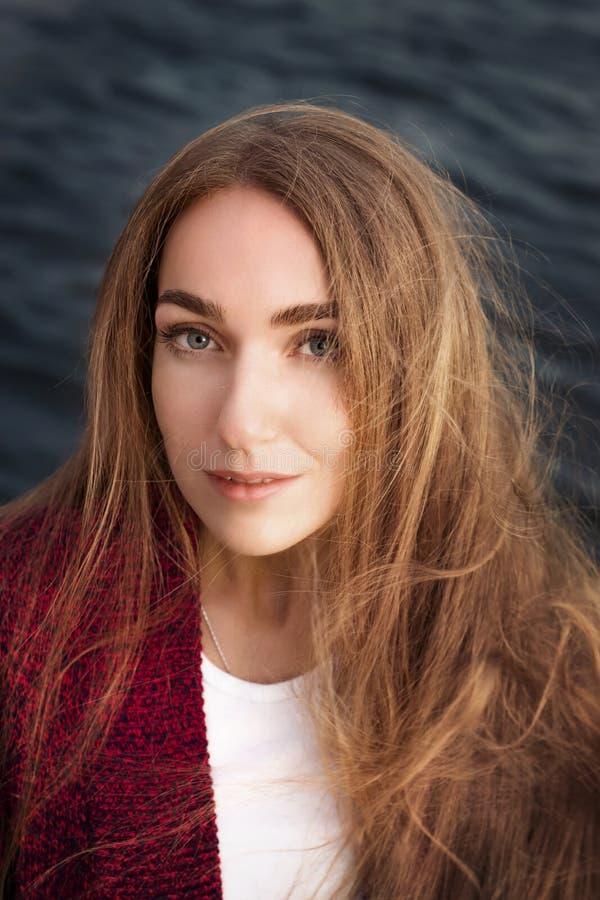 Mujer joven con el pelo salvaje largo contra el agua oscura imagen de archivo