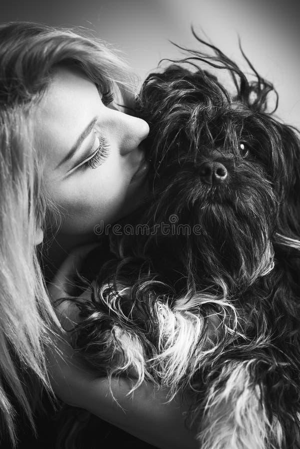 Mujer joven con el perro lindo peludo fotografía de archivo