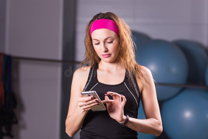Mujer joven con el perseguidor en el gimnasio, rotura del smartphone y de la aptitud del entrenamiento fotos de archivo libres de regalías