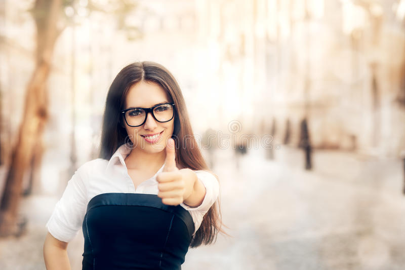 Mujer joven con el pulgar de los vidrios para arriba fotos de archivo libres de regalías