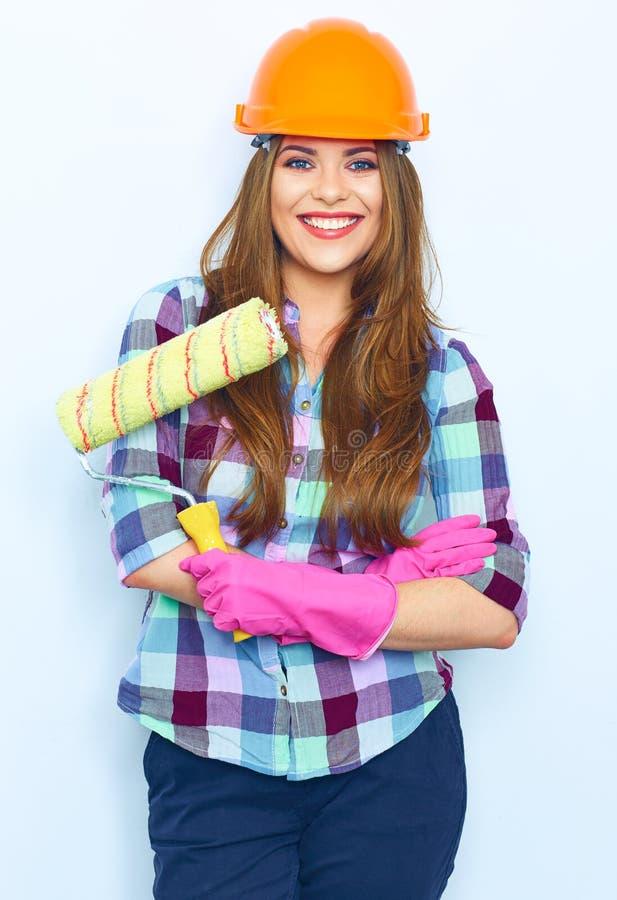 Mujer joven con el rodillo de pintura cruzado de la tenencia de brazos imagen de archivo