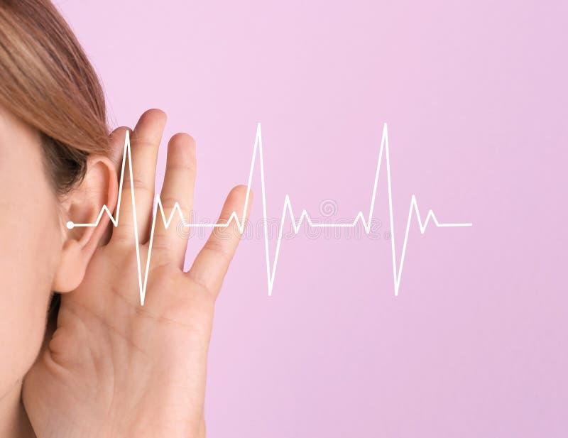 Mujer joven con el síntoma de la pérdida de oído fotografía de archivo