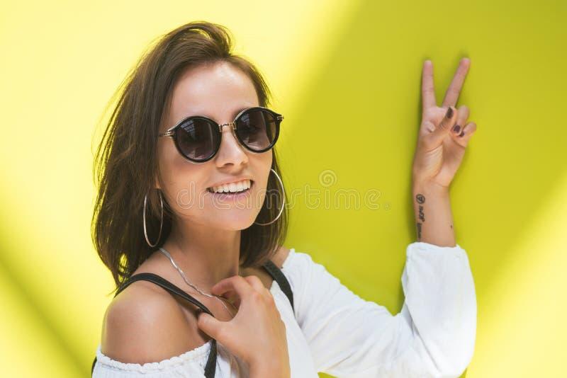 Mujer joven con el signo de la paz delante de la pared amarilla Muchacha de moda con las gafas de sol fotos de archivo
