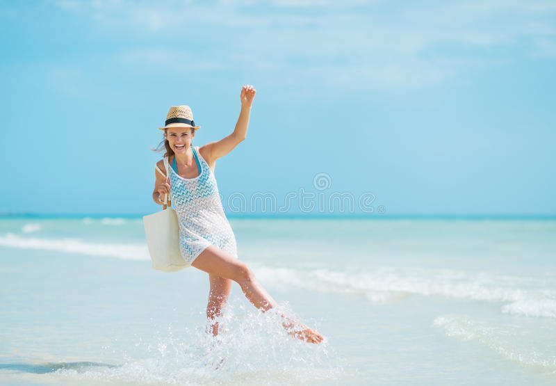 Mujer joven con el sombrero y bolso que tiene tiempo de la diversión en la playa fotografía de archivo