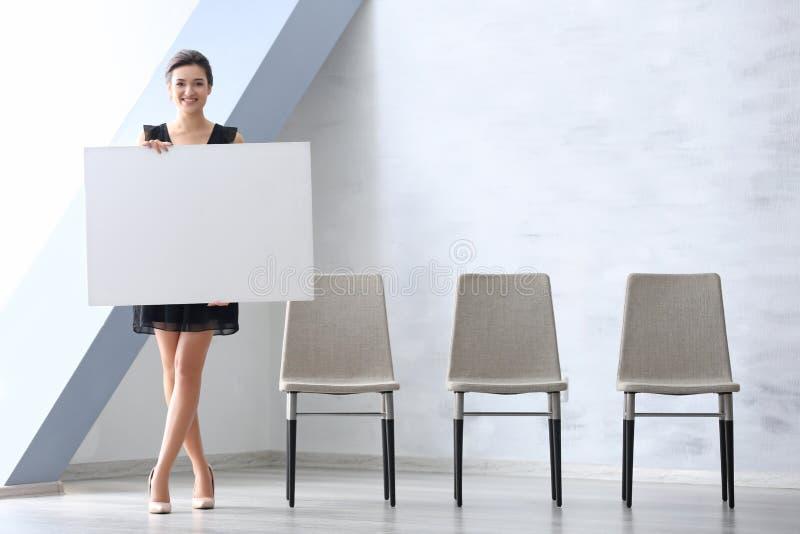 Mujer joven con el tablero de publicidad en blanco imagen de archivo
