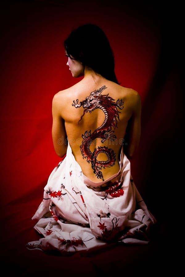 Mujer joven con el tatuaje del dragón fotografía de archivo