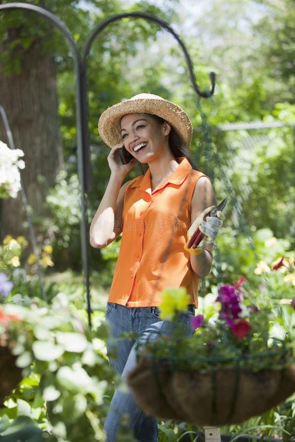 Mujer joven con el teléfono celular en jardín imagen de archivo libre de regalías