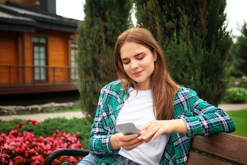 Mujer joven con el teléfono móvil que descansa sobre banco de madera en parque fotos de archivo libres de regalías