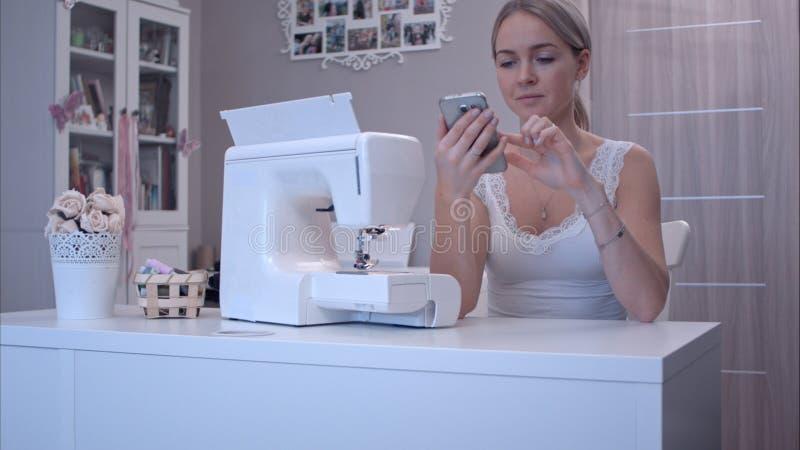 Mujer joven con el teléfono que se sienta en la tabla al lado de la máquina de coser imagen de archivo