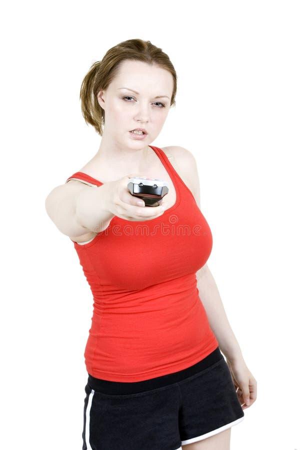 Mujer joven con el telecontrol de la TV que parece enojado imagen de archivo libre de regalías