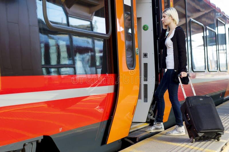 Mujer joven con el tren rodado del embarque del equipaje foto de archivo
