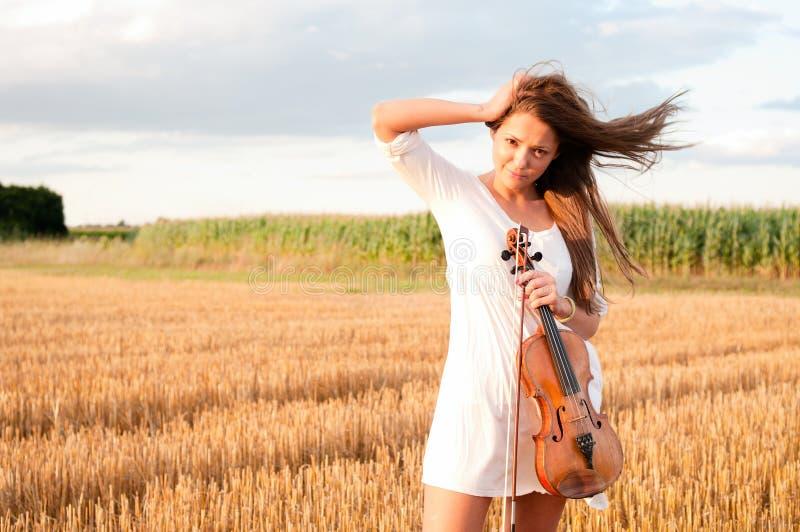 Mujer joven con el violín al aire libre fotografía de archivo