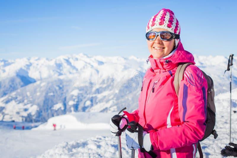 Mujer joven con esquís y un desgaste del esquí fotos de archivo