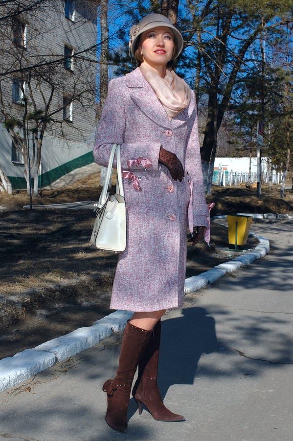 Mujer joven con estilo en capa y el sombrero de la señora. foto de archivo