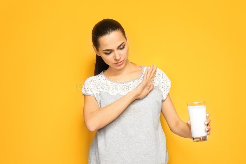 Mujer joven con la alergia de la lechería que sostiene el vidrio de leche fotos de archivo
