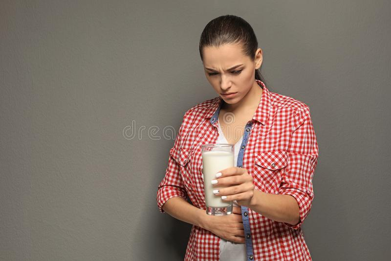 Mujer joven con la alergia de la lechería que sostiene el vidrio de leche fotos de archivo libres de regalías