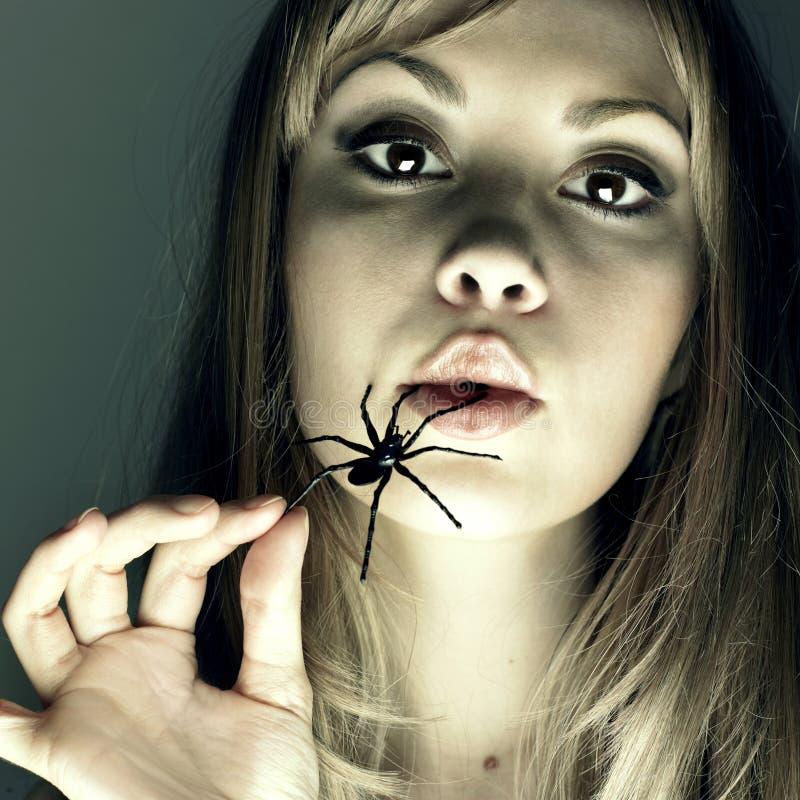 Mujer joven con la araña en una boca fotografía de archivo