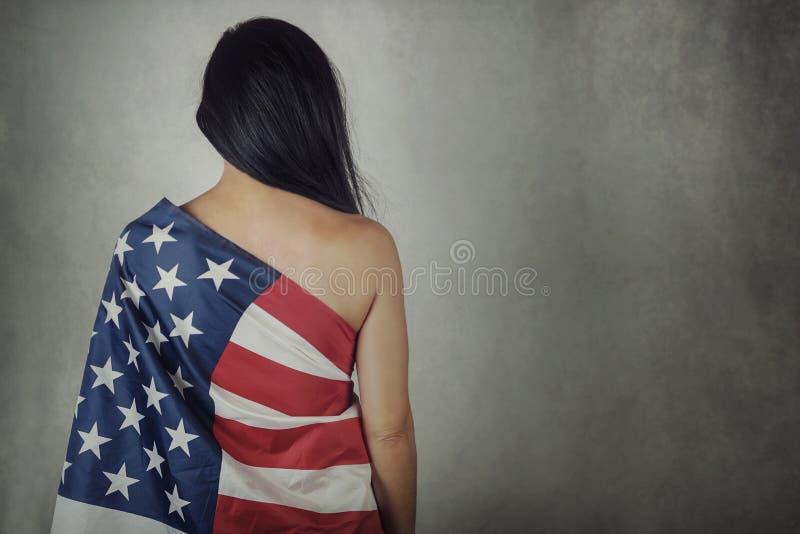 Mujer joven con la bandera americana fotografía de archivo