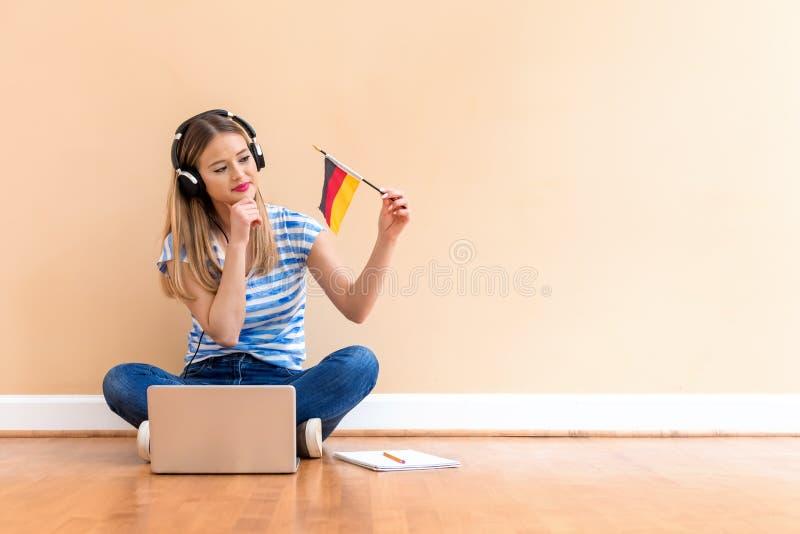 Mujer joven con la bandera de Alemania usando un ordenador portátil imágenes de archivo libres de regalías
