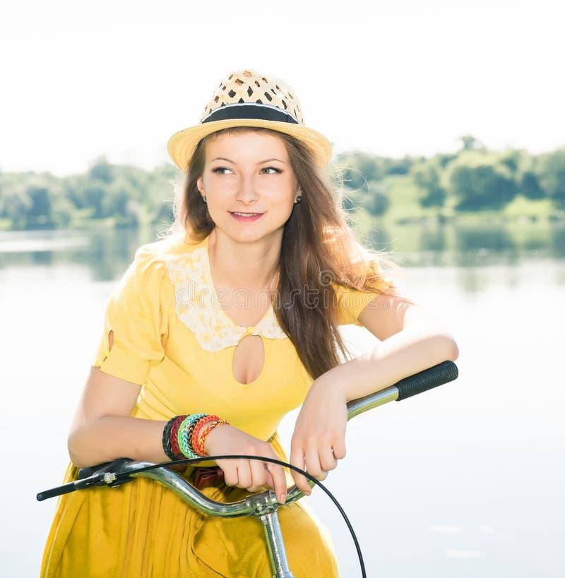 Mujer joven con la bici del vintage en una carretera nacional cerca del lago O foto de archivo libre de regalías