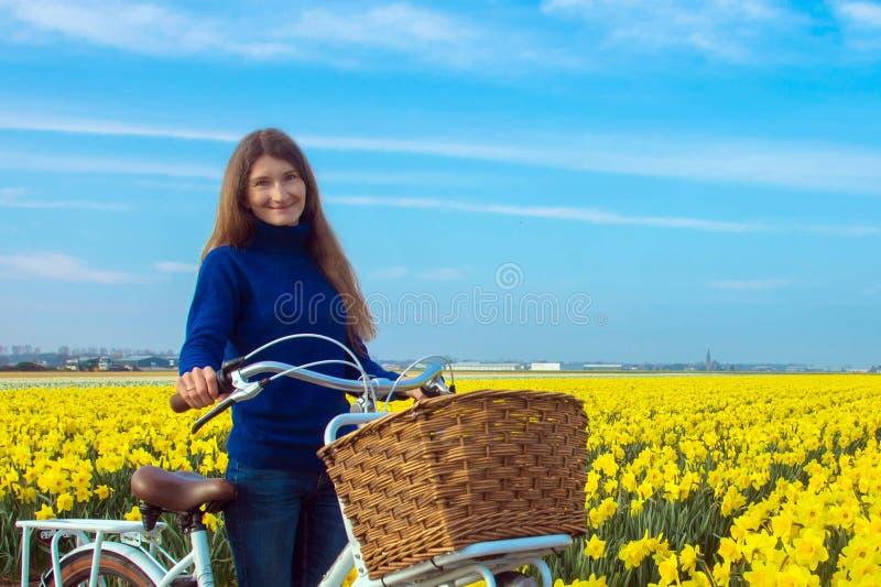 Mujer joven con la bicicleta en el fondo de la primavera floreciente imagen de archivo