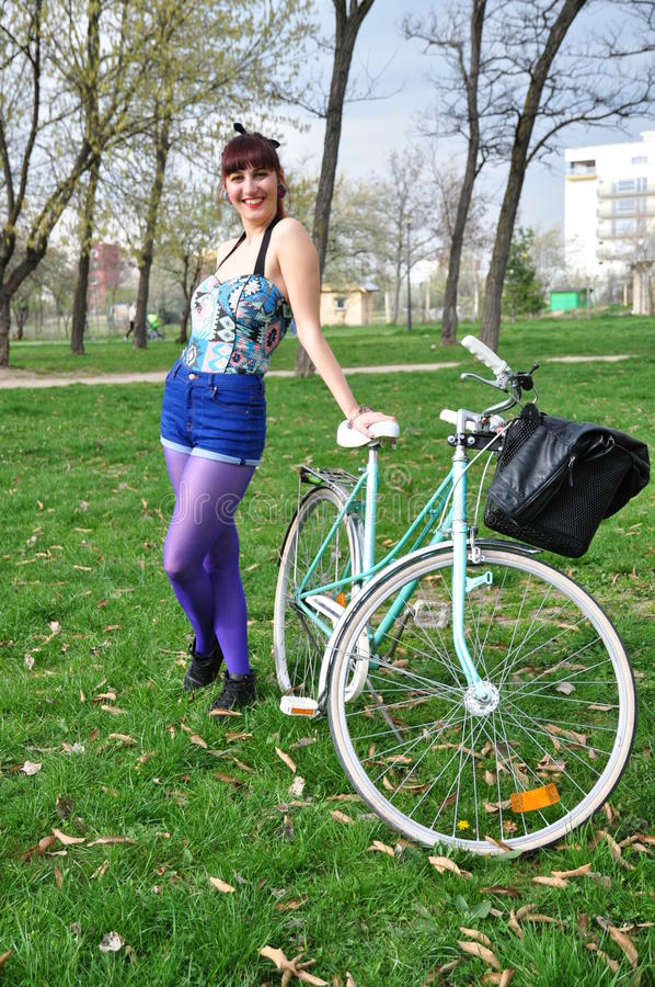 Mujer joven con la bicicleta en un parque fotografía de archivo libre de regalías