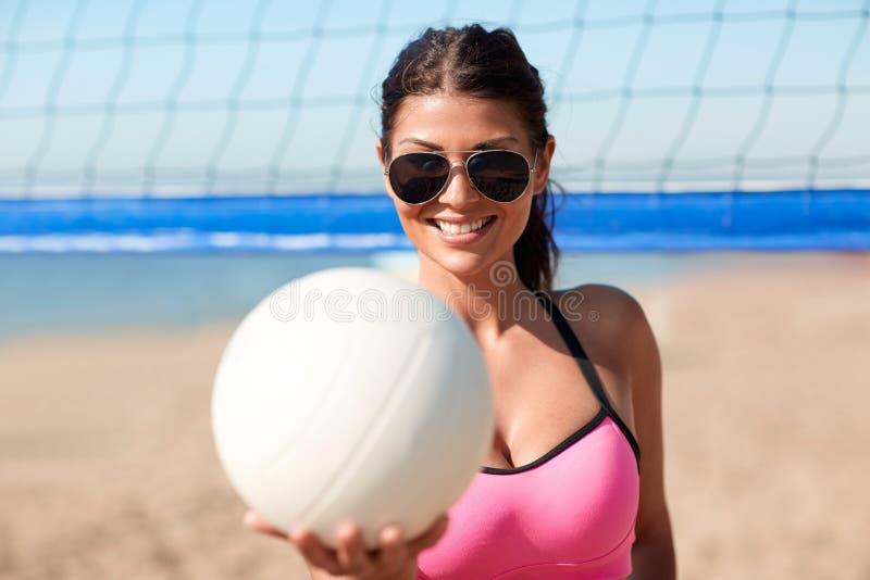 Mujer joven con la bola del voleibol y red en la playa foto de archivo libre de regalías
