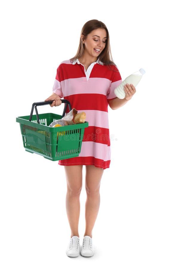 Mujer joven con la botella de leche y de hacer compras aislados en blanco foto de archivo