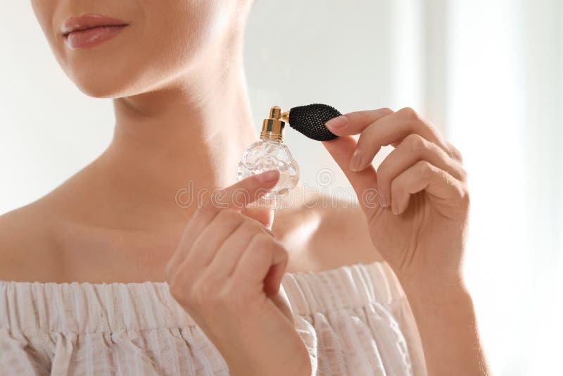 Mujer joven con la botella de perfume en fondo borroso imagen de archivo libre de regalías