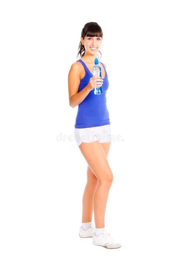 Mujer joven con la botella en la mano después de la aptitud. imagen de archivo