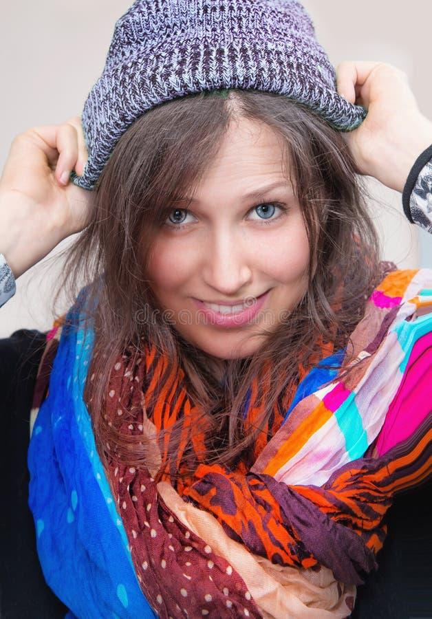 Mujer joven con la bufanda colorida y el casquillo gris fotos de archivo