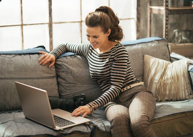 Mujer joven con la cámara de la foto del dslr usando el ordenador portátil fotografía de archivo libre de regalías