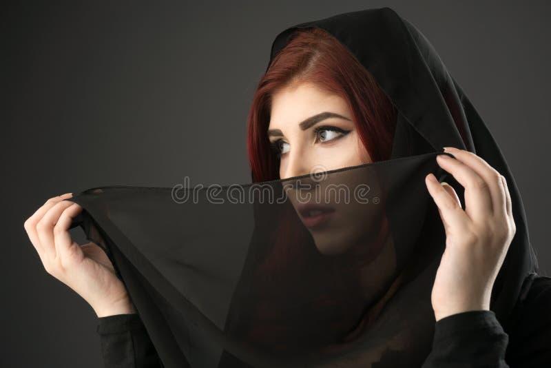 Mujer joven con la cabeza cubierta por un velo negro fotografía de archivo