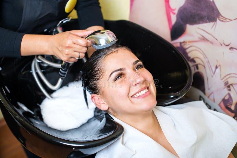 Mujer joven con la cabeza que se lava del peluquero en el salón de pelo imagenes de archivo