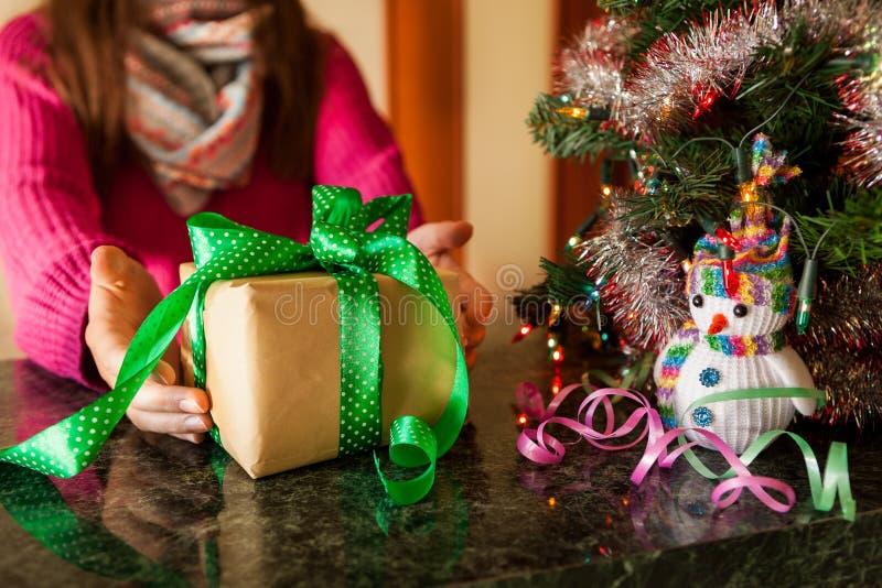 Mujer joven con la caja de regalo cerca del árbol de navidad, Feliz Año Nuevo imagen de archivo libre de regalías