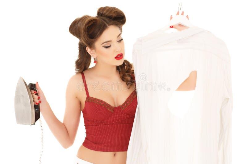 Mujer joven con la camisa y el hierro foto de archivo