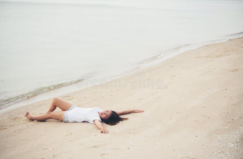 Mujer joven con la camiseta blanca que se acuesta en la playa Sonrisa imagen de archivo