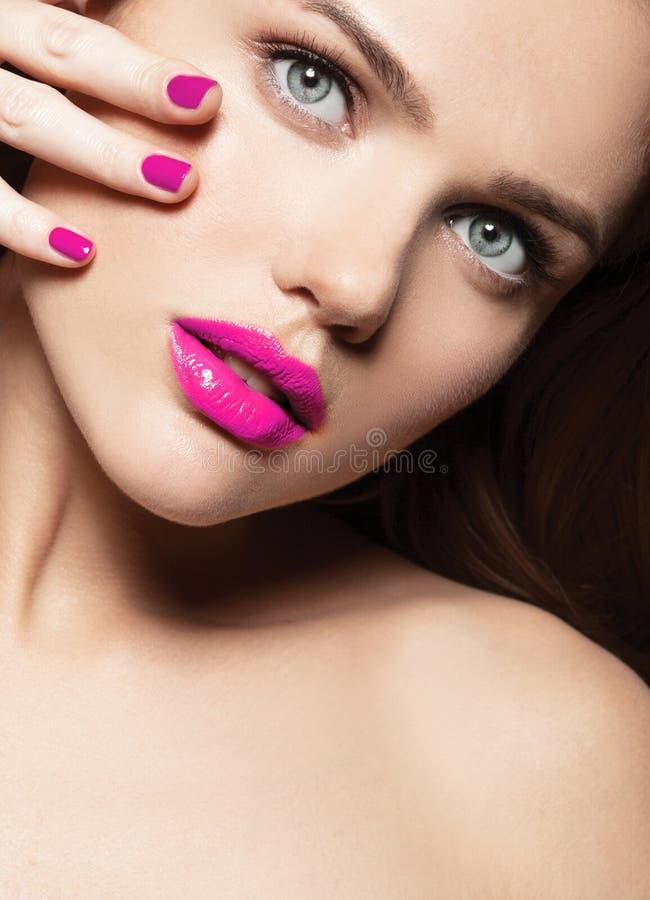 Mujer joven con la cara sana hermosa con el lápiz labial rosado fotografía de archivo libre de regalías