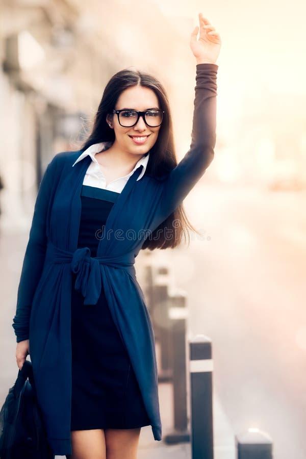 Mujer joven con la cartera que llama un taxi imágenes de archivo libres de regalías
