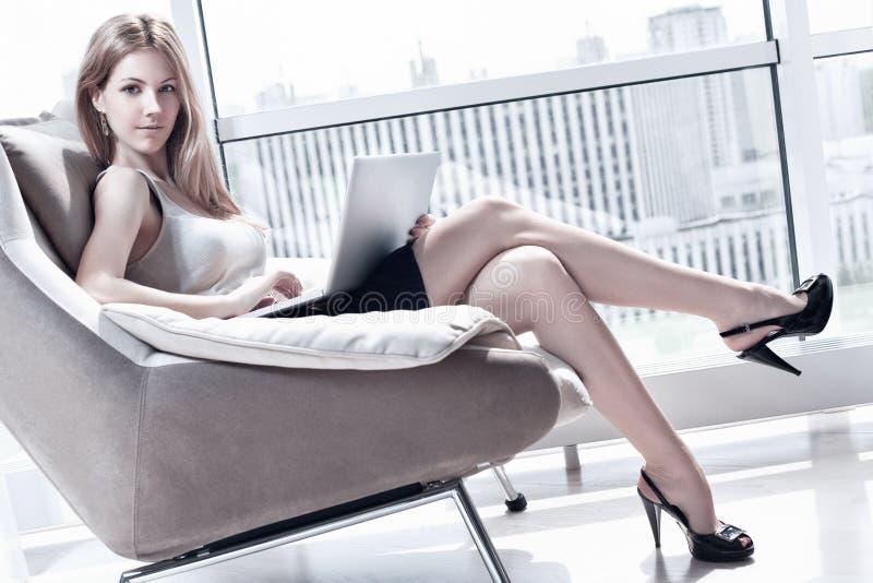Mujer joven con la computadora portátil imagen de archivo libre de regalías