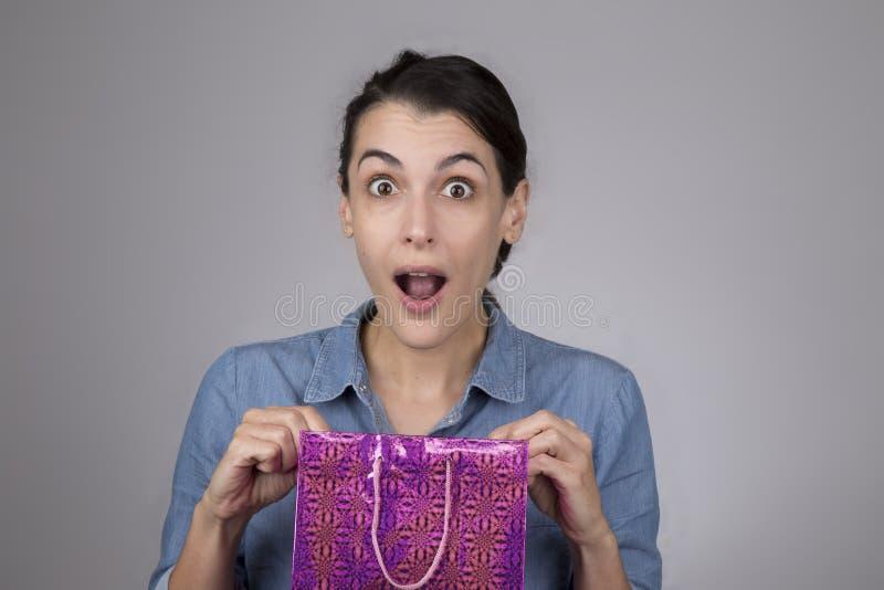 mujer joven con la expresión sorprendida en su cara como ella abre el bolso del regalo fotografía de archivo libre de regalías