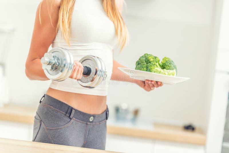 Mujer joven con la figura de los deportes en la cocina que lleva a cabo pesas de gimnasia en sus manos y una placa del bróculi foto de archivo libre de regalías