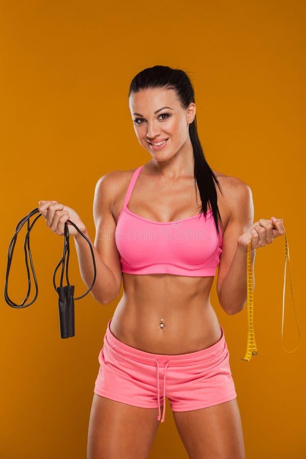 Mujer joven, con la figura deportiva sana con imagen de archivo
