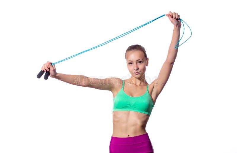 Mujer joven con la figura deportiva sana que lleva a cabo la cuerda que salta fotografía de archivo