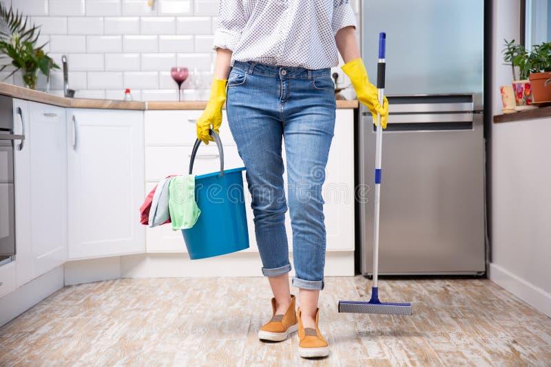 Mujer joven con la fregona y detergentes en la cocina, primer servicio de la limpieza fotos de archivo libres de regalías
