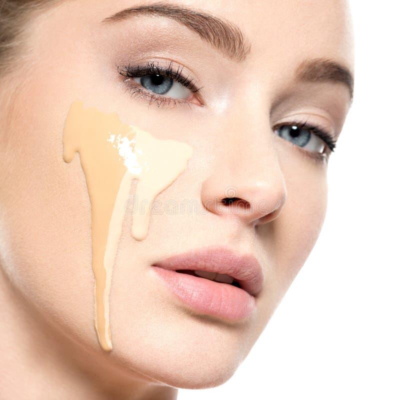 Mujer joven con la fundación cosmética en piel imagen de archivo